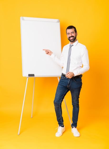 Foto de corpo inteiro do empresário dando uma apresentação no quadro branco sobre o dedo apontando amarelo isolado para o lado Foto Premium