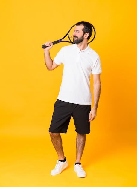 Foto de corpo inteiro do homem ao longo da parede amarela isolada, jogando tênis e olhando para cima Foto Premium