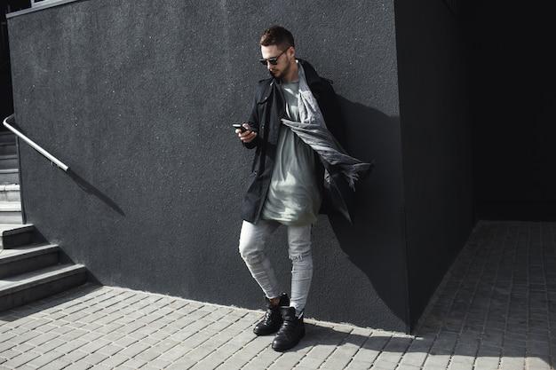 Foto de corpo inteiro do homem na mensagem de mensagens de texto do casaco lá fora. Foto gratuita
