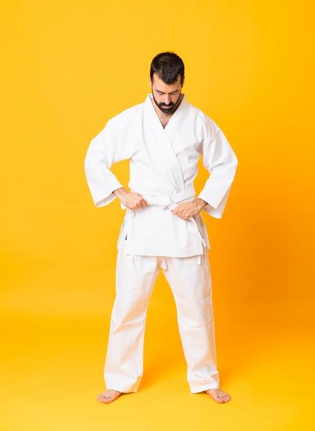 Foto de corpo inteiro do homem sobre fundo amarelo isolado, fazendo karatê Foto Premium