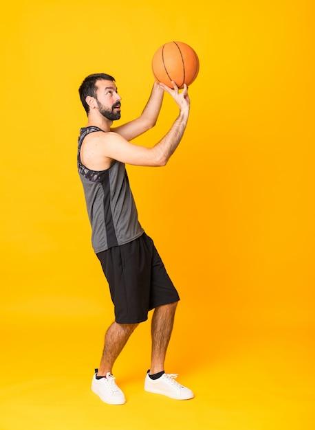 Foto de corpo inteiro do homem sobre fundo amarelo isolado jogando basquete Foto Premium
