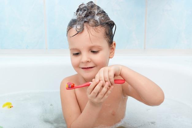Foto de criança escovando os dentes enquanto estiver a tomar banho, encantadora senhora molhada segura a escova de dente vermelha Foto gratuita