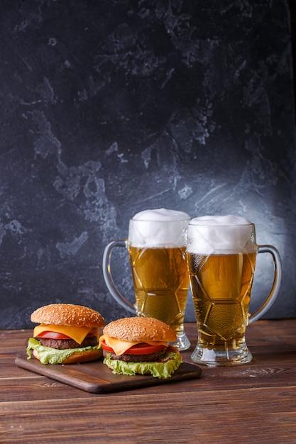 Foto de dois hambúrgueres, copos com cerveja Foto Premium
