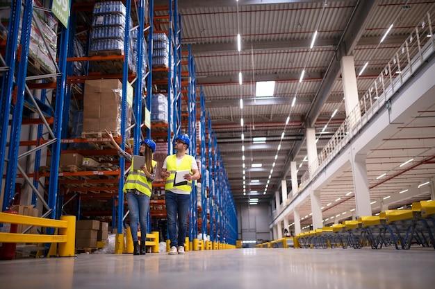 Foto de dois trabalhadores caminhando por um grande centro de depósito, observando prateleiras com produtos e planejando a distribuição para o mercado Foto gratuita