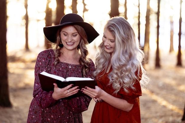 Foto de duas mulheres posando com um livro na floresta, clima de outono Foto gratuita