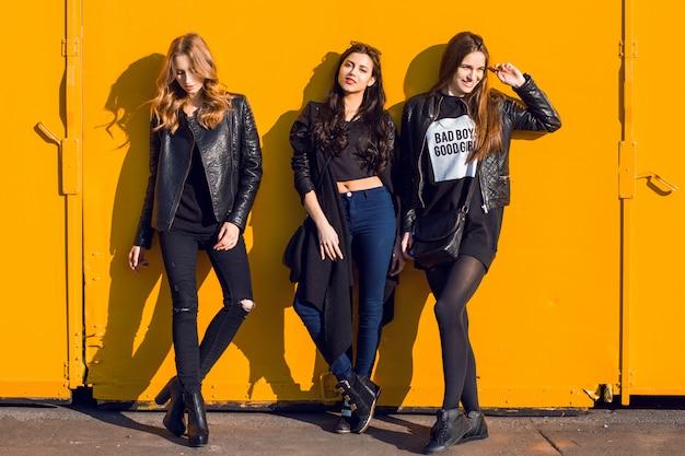 Foto de estilo de vida de moda de três meninas elegantes em roupa de primavera negra, posando contra uma parede rosa urbana. Foto gratuita