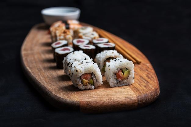 Foto de estoque da composição de sushi com maki, california roll e nigiri com palitos e salsa de soja sobre a mesa de madeira. Foto Premium