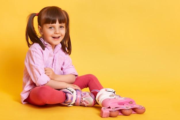 Foto de estúdio da menina sorridente feliz sentada no chão Foto gratuita