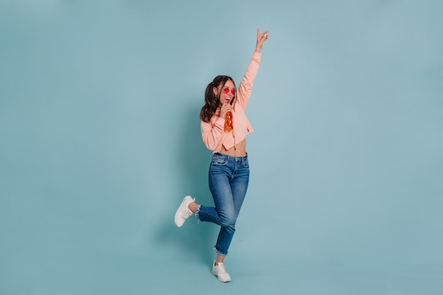 Foto de estúdio de corpo inteiro de uma jovem atraente vestindo pulôver rosa e óculos redondos rosa dançando e bebendo suco sobre uma parede isolada Foto gratuita