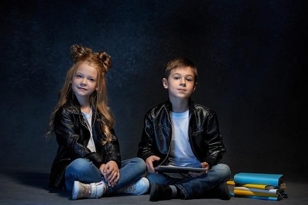 Foto de estúdio de duas crianças com um tablet sentado no chão Foto gratuita