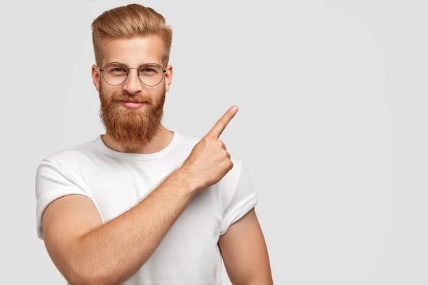 Foto de estúdio de gengibre hippie com barba grossa, corte de cabelo da moda, tem uma expressão séria, aponta com o dedo indicador no canto superior direito Foto gratuita