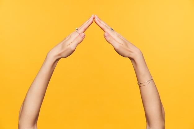 Foto de estúdio de mãos bem cuidadas de jovem fêmea dobrando-se juntas enquanto imita o telhado da casa, isolado sobre o fundo amarelo. conceito de mãos de mulher Foto gratuita