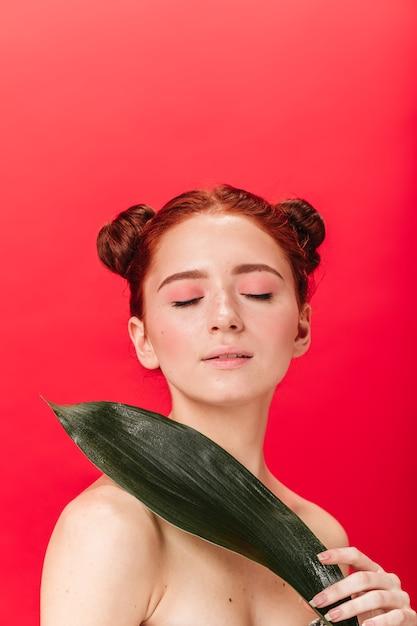 Foto de estúdio de menina caucasiana, segurando uma folha verde com os olhos fechados. mulher nua de gengibre com planta isolada em fundo vermelho. Foto gratuita
