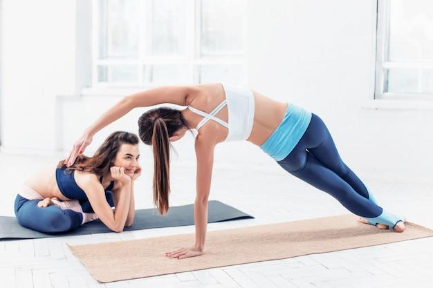 Foto de estúdio de um jovem apto mulheres fazendo exercícios de ioga Foto gratuita