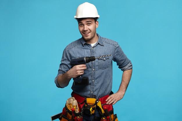 Foto de estúdio de um jovem construtor amigável carregando a broca e o cinto com todos os instrumentos fazendo reformas para o cliente Foto gratuita
