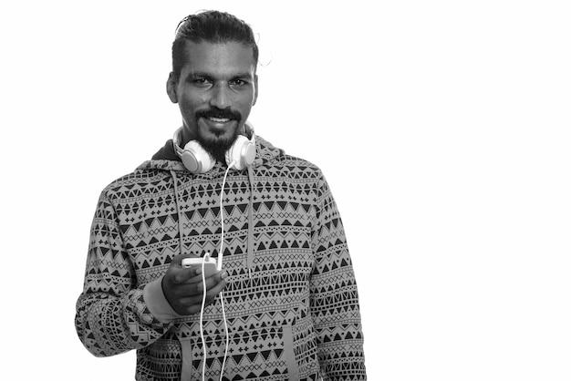 Foto de estúdio de um jovem indiano barbudo bonito usando um capuz contra o branco em preto e branco Foto Premium