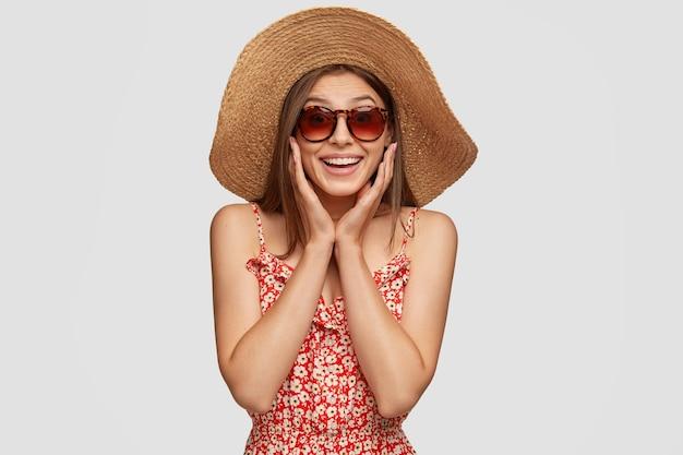 Foto de estúdio de um lindo turista satisfeito passando as férias de verão no exterior, sorrindo enquanto faz uma excursão maravilhosa e usando óculos escuros Foto gratuita