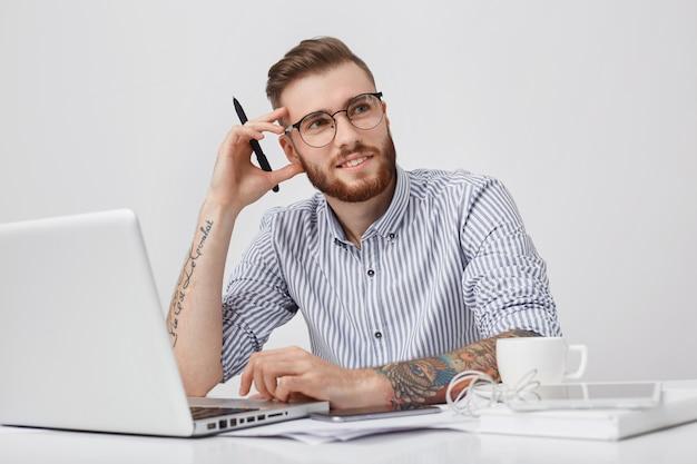 Foto de estúdio de um trabalhador do sexo masculino criativo pensativo ou teclados de jornalista em um laptop, Foto gratuita
