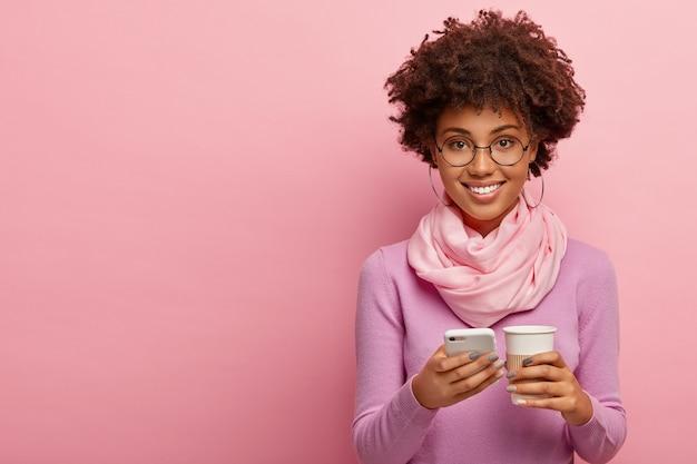 Foto de estúdio de uma mulher afro-americana encantada que navega na internet no smartphone, verifica o feed de notícias, gosta de beber café aromático em um copo de papel, usa roupas da moda e óculos redondos Foto gratuita