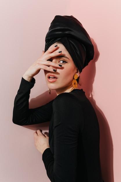 Foto de estúdio de uma mulher sensual usando brincos de ouro Foto gratuita