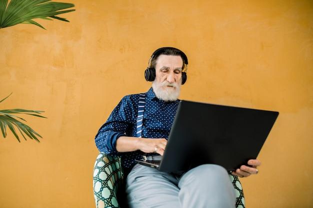Foto de estúdio do homem sênior concentrado bonito em roupas elegantes, usando fones de ouvido, sentado na cadeira e usando o computador portátil Foto Premium