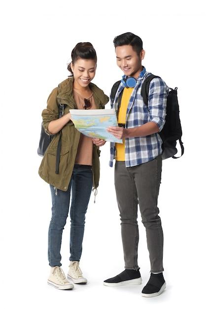 Foto de estúdio do jovem casal com mochilas navegando no mapa contra fundo branco Foto gratuita