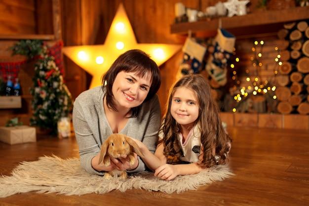 Foto de família de mãe e filha, deitado no chão na lareira com coelho fofo. decoração de natal Foto Premium
