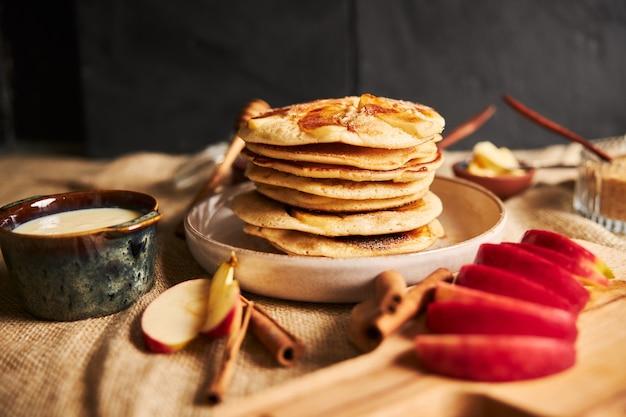 Foto de foco seletivo de panquecas de maçã com maçãs e outros ingredientes na mesa Foto gratuita