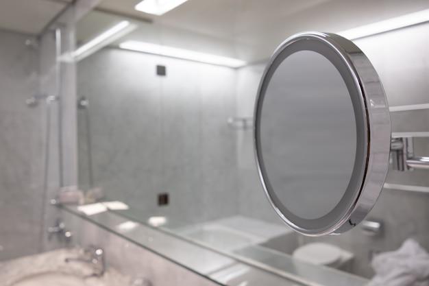 Foto de foco seletivo do espelho no banheiro com interior branco Foto gratuita
