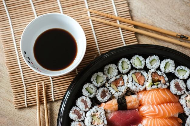Foto de foco seletivo dos deliciosos rolos de sushi servidos em um prato preto redondo Foto gratuita