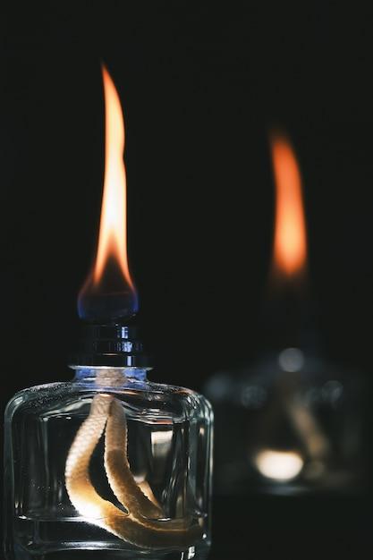 Foto de foco seletivo vertical de dois isqueiros a álcool isolados em um fundo preto Foto gratuita