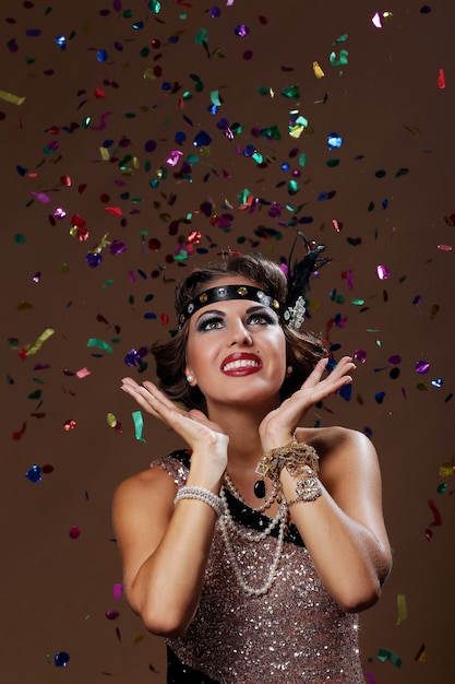 Foto de fundo de confetes de mulher festa em estúdio Foto gratuita