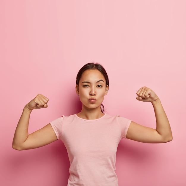 Foto de garota asiática séria e autoconfiante mantém os lábios dobrados, mostra seus músculos e força, não usa maquiagem, vestida com uma camiseta casual, isolada na parede rosa com espaço de cópia acima para obter informações Foto gratuita