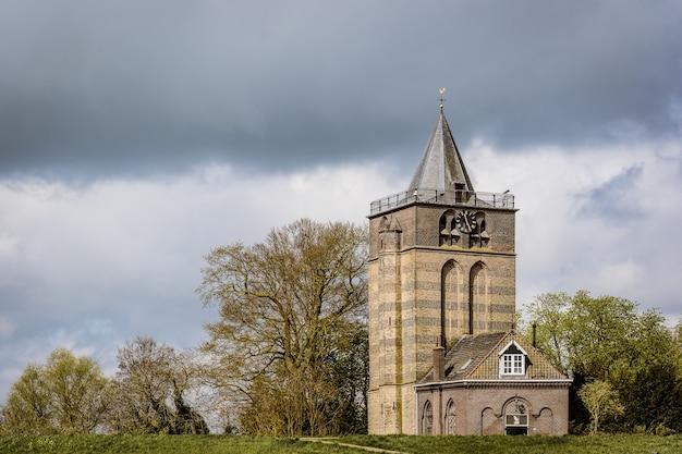 Foto de grande angular de um edifício sob um céu nublado e cercado por árvores Foto gratuita