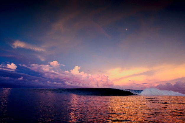 Foto de grande angular de um pôr do sol hipnotizante no oceano sob um céu cheio de nuvens multicoloridas Foto gratuita