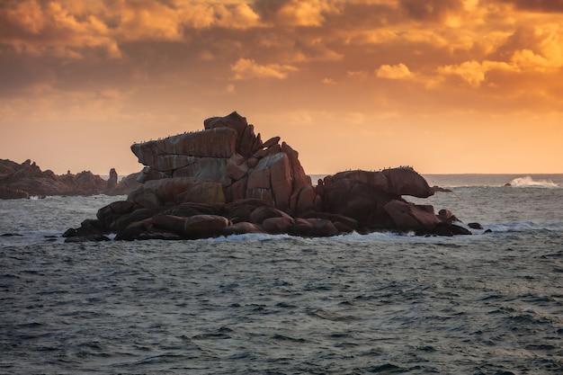 Foto de grande angular de uma ilha de penhascos cercada pela água durante o pôr do sol Foto gratuita
