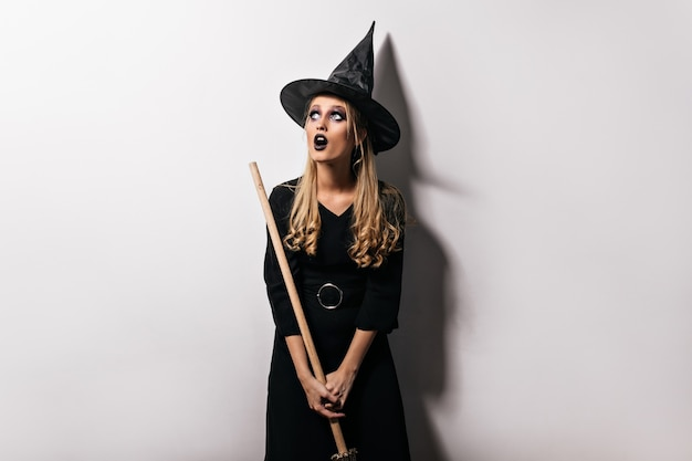 Foto de halloween de uma menina bonita loira com vassoura mágica. foto interna da curiosa jovem bruxa de chapéu preto. Foto gratuita