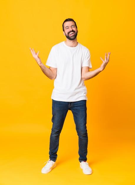 Foto de homem com barba sobre fundo amarelo isolado, sorrindo muito Foto Premium