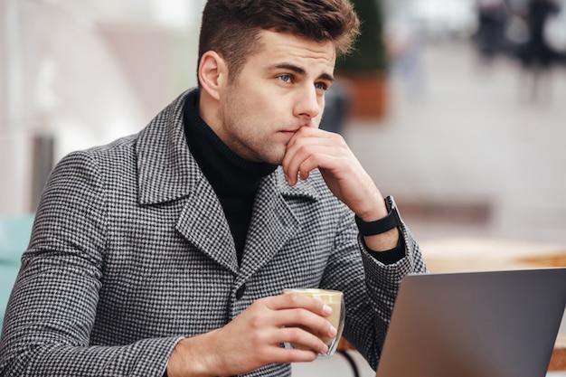 Foto de homem de negócios concentrado trabalhando com laptop prata no café lá fora, tomando café no copo Foto gratuita