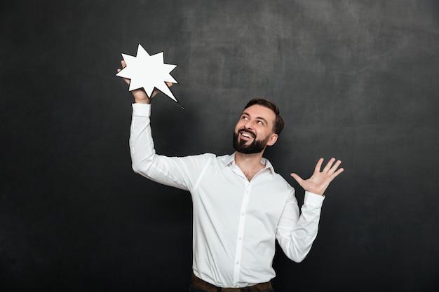 Foto de homem encantado, segurando a estrela do discurso em branco e olhando de lado por cima da parede cinza escura, cópia espaço Foto gratuita