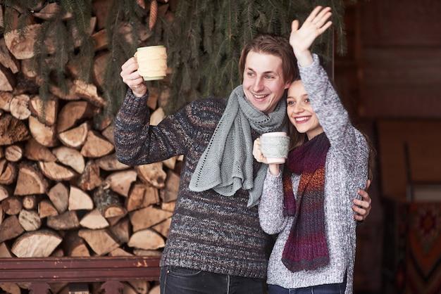 Foto de homem feliz e mulher bonita com copos ao ar livre no inverno. férias de inverno e férias. casal de natal de homem e mulher feliz bebem café quente. olá vizinhos Foto Premium