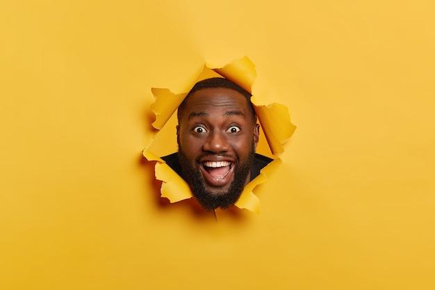 Foto de homem negro feliz com expressão facial satisfeita, cerdas escuras, se diverte dentro de casa, mantém a cabeça no buraco do papel rasgado, ri e olha para a câmera, isolada sobre fundo amarelo. Foto gratuita