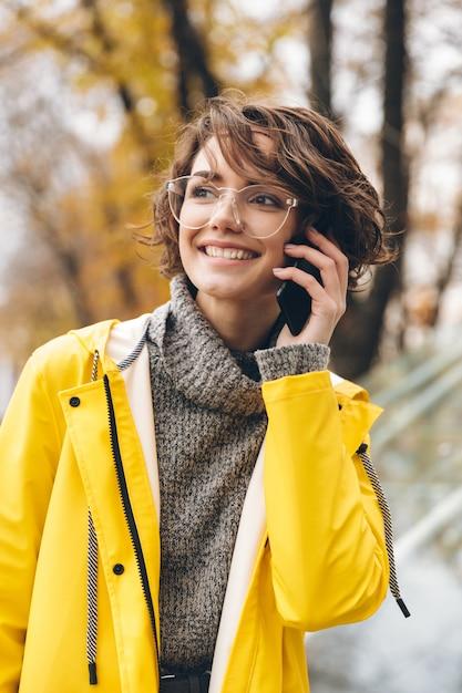 Foto de jovem de capa de chuva amarela e óculos passar um tempo fora tendo uma agradável conversa móvel Foto gratuita