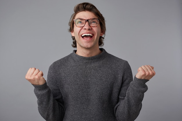 Foto de jovem feliz com óculos usa suéter cinza, fica sobre um fundo cinza. sorri amplamente e aperta os punhos, ganhou o milhão e sente felicidade. Foto gratuita