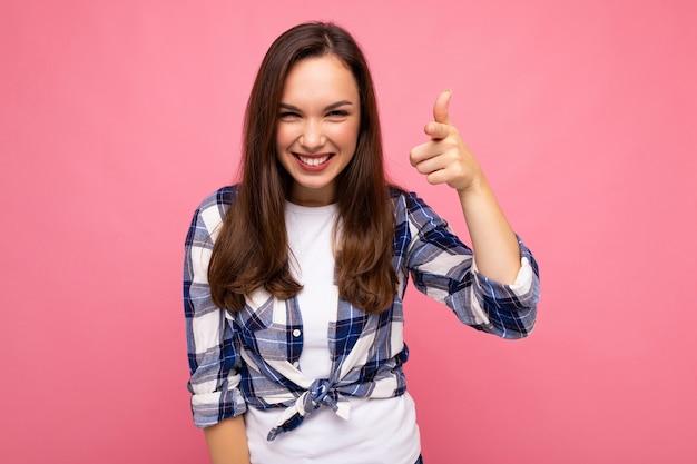 Foto de jovem feliz sorridente linda mulher morena com emoções sinceras, vestindo a camisa da moda isolada no fundo rosa com espaço vazio. Foto Premium