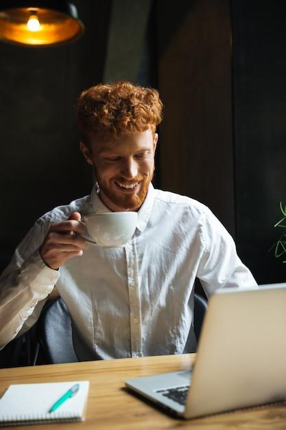 Foto de jovem ruiva sorridente homem barbudo segurando a xícara de café, olhando para a tela do laptop enquanto trabalhava na cafeteria Foto gratuita