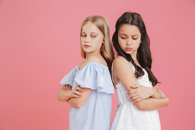 Foto de meninas morenas e loiras de 8 a 10 anos de idade usando vestidos de costas um para o outro com os braços cruzados e expressando briga, isolada sobre um fundo rosa Foto Premium