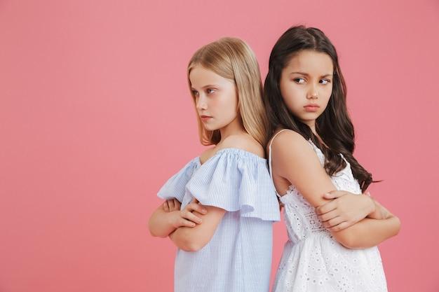 Foto de meninas morenas e loiras ofendidas de 8 a 10 anos de idade usando vestidos de costas um para o outro com os braços cruzados e expressando argumento, isolada sobre um fundo rosa Foto Premium