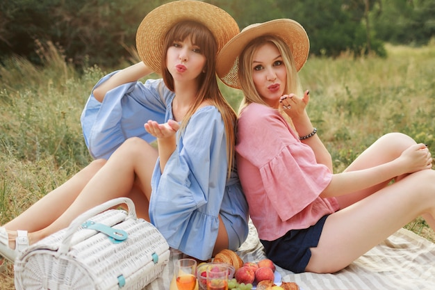 Foto de moda ao ar livre de duas mulheres atraentes com chapéu de palha e roupas de verão desfrutando de piknik. Foto gratuita
