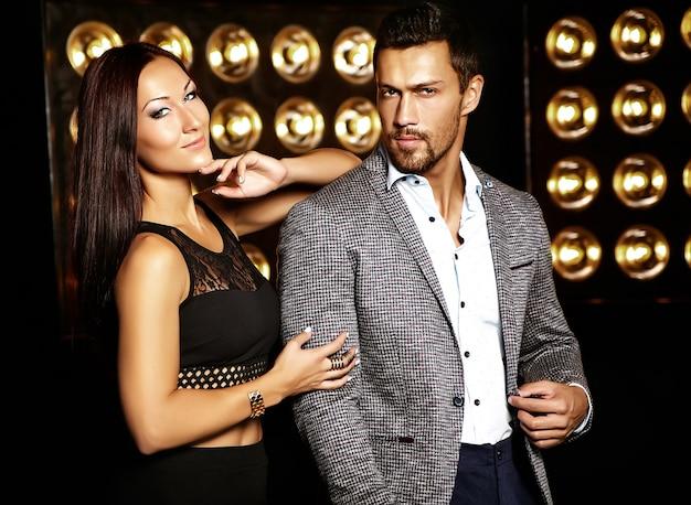 Foto de moda de homem elegante bonito de terno com bela mulher sexy, posando em fundo preto luzes de estúdio Foto gratuita